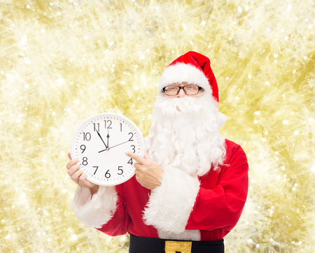 twelve month old: christmas, holidays and people concept - man in costume of santa claus with clock showing twelve pointing finger over yellow lights background