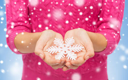 christmas, holidays and people concept - close up of woman in pink sweater holding snowflake decoration over blue background with snow photo