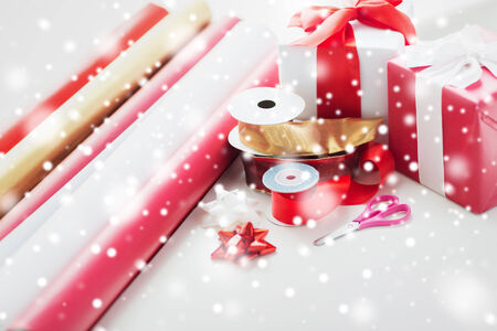 x mas: holidays and celebration concept - close up of christmas presents, decoration paper, ribbons and scissors