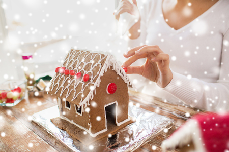 christmas cooking: cooking, people, christmas and decoration concept - close up of happy woman making gingerbread houses at home
