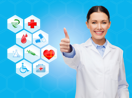 healthcare, medicine, people, gesture and symbols concept - smiling young female doctor or nurse showing thumbs up over medical icons and blue background photo