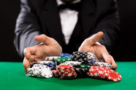 fichas de casino: casino, el juego, el p�quer, la gente y el concepto de entretenimiento - Cierre de jugador de p�ker con fichas en la mesa de casino verde Foto de archivo