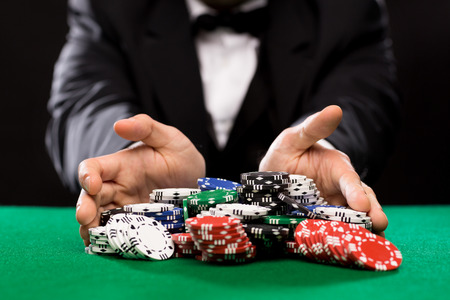 casino dealer: casino, gambling, poker, people and entertainment concept - close up of poker player with chips at green casino table