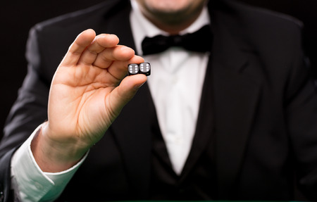 double the chances: gambling, fortune, casino and entertainment concept - close up of man showing dice with double six over black background