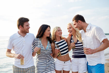 non alcoholic beer: summer, holidays, tourism, drinks and people concept - group of smiling friends with bottles drinking beer or cider on beach Stock Photo