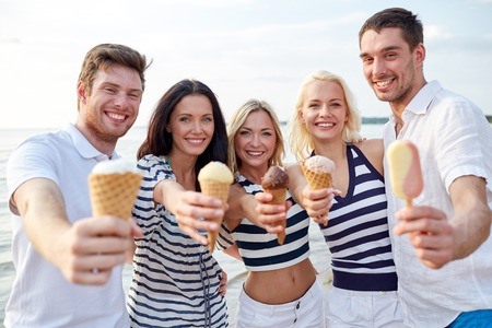 enjoying: summer, holidays, sea, tourism and people concept - group of smiling friends showing ice cream on beach