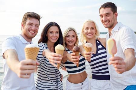 comiendo helado: verano, las vacaciones, el mar, el turismo y la gente concepto - grupo de amigos sonrientes que muestran el helado en la playa Foto de archivo