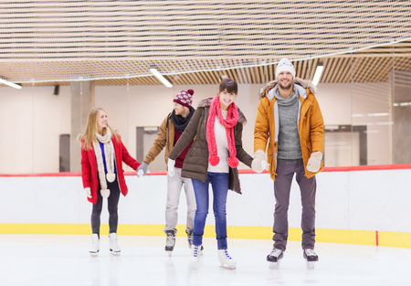 ice skating: people, friendship, sport and leisure concept - happy friends on skating rink