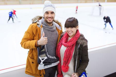 patinando: la gente, la amistad, el deporte y el concepto de ocio - pareja feliz con patines de hielo en la pista de patinaje