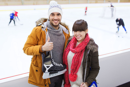 ice skate: people, friendship, sport and leisure concept - happy couple with ice-skates on skating rink