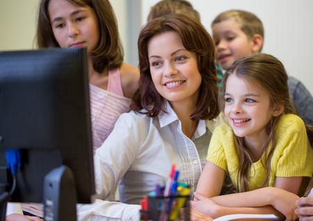 salon de clase: educaci�n, escuela primaria, el aprendizaje, la tecnolog�a y el concepto de la gente - grupo de ni�os de la escuela con el maestro en busca de monitor de la computadora en el aula