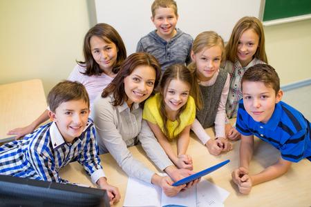 educacion: educación, escuela primaria, el aprendizaje, la tecnología y el concepto de la gente - grupo de niños de la escuela y el maestro con el ordenador Tablet PC en el aula Foto de archivo