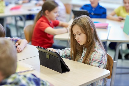 education, elementary school, learning, technology and people concept - little schoolgirl with tablet pc computer on break in classroom