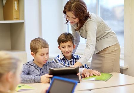 salon de clases: educación, escuela primaria, el aprendizaje y la gente conceptuales - ayuda del profesor de niños de la escuela con la computadora Tablet PC en el aula