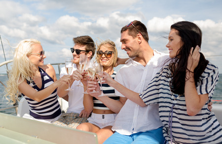 yacht people: vacation, travel, sea, friendship and people concept - smiling friends with glasses of champagne on yacht