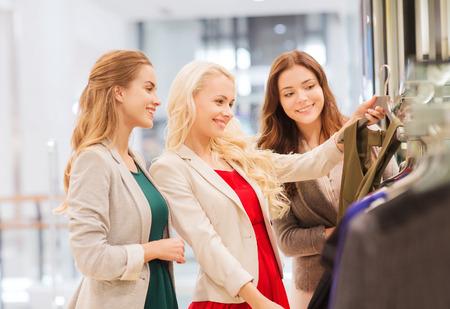 centro comercial: venta, el consumismo y el concepto de la gente - mujeres j�venes felices que eligen la ropa en centro comercial