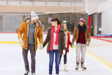 skating fun: people, friendship, sport and leisure concept - happy friends on skating rink