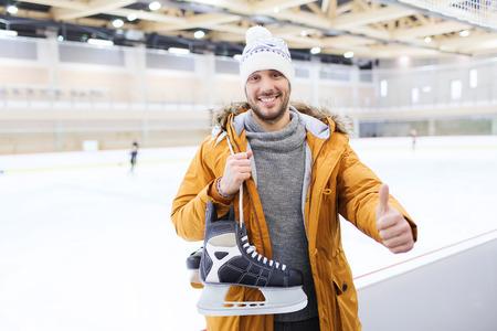 patinaje sobre hielo: la gente, el deporte, el gesto y el concepto de ocio - joven feliz con patines de hielo que muestran los pulgares para arriba en la pista de patinaje
