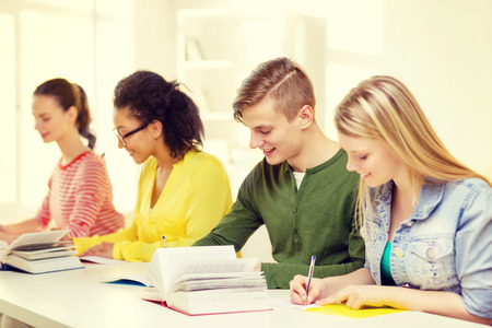 education and school concept - five smiling students with textbooks and books at school photo