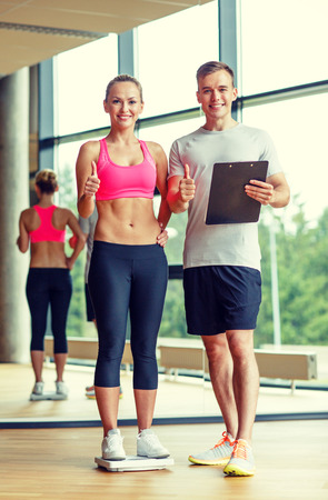 sport, fitness, lifestyle and people concept - smiling man and woman with scales and clipboard showing thumbs up in gym photo