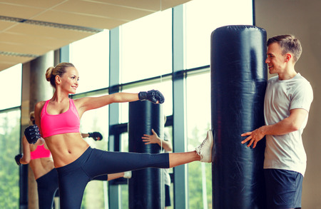 kick: sport, fitness, lifestyle and people concept - smiling woman with personal trainer boxing in gym