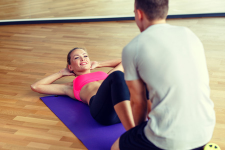 sport, fitness, lifestyle and people concept - smiling woman with male personal trainer exercising in gym photo