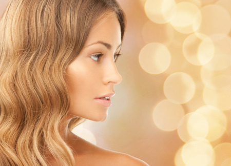 beauty, people and health concept - beautiful young woman face over beige lights background Stock Photo