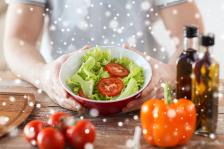 cooking, people, food, vegetarian and home concept - close of male hands holding bowl with salad