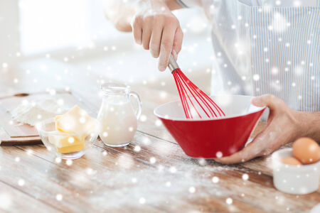 whipping: cooking, food, people and home concept - close up of man whipping eggs or cream with whisk in bowl