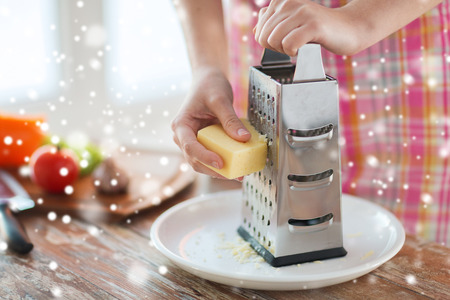 shredding: cooking, food, people and home concept - close up of female hands with grater and vegetables grating cheese in kitchen
