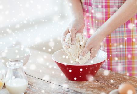 haciendo pan: cocinar, hornear, la comida, la gente y el concepto de la casa - cerca de las manos femeninas que amasan la pasta en la cocina