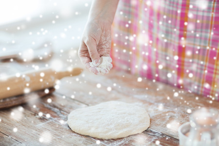 cooking and home concept - close up of female hand sprinkling dough with flour photo