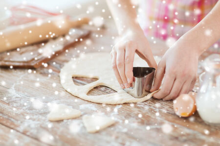 cooking, baking, people and home concept - close up of woman hands making cookies from fresh dough at home photo