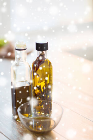 vinegar bottle: cooking and food concept - close up of two olive oil bottles and glass bowl on wooden table at home kitchen