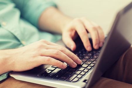 klawiatury: technologii, do domu i stylu życia koncepcji - bliska człowiek pracy z komputera przenośnego i siedzi na kanapie w domu