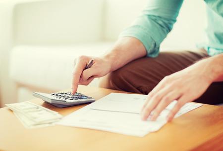 renta: ahorros, las finanzas, la econom�a y el hogar concepto - cerca del hombre con la calculadora contar dinero y haciendo notas en casa