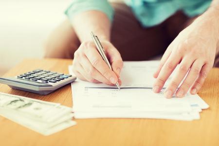 úspory, finance, ekonomika a domácí koncept - close up člověka s počítání kalkulačka peníze a dělala si poznámky doma