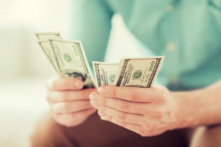 contando dinero: ahorros, las finanzas, la econom�a y el hogar concepto - cerca de hombre contando dinero en casa