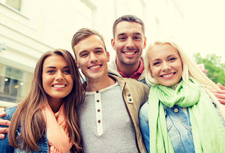 four people: travel, vacation and friendship concept - group of smiling friends in city