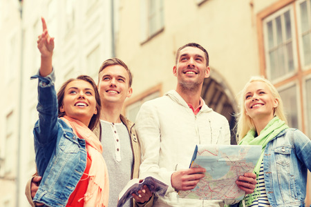 woman pointing up: travel, vacation and friendship concept - group of smiling friends with city guide and map exploring city