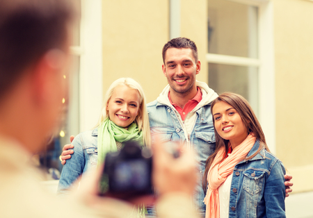 group picture: travel, vacation, technology and friendship concept - guy picturing group of friends in city Stock Photo