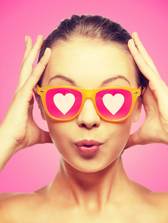 love, happiness, valentines day, face expressions and people concept - portrait of surprised teenage girl in pink sunglasses with hearts photo