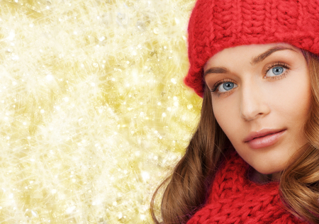 yellow fleece: happiness, winter holidays, christmas and people concept - close up of smiling young woman in red hat and scarf over yellow lights background