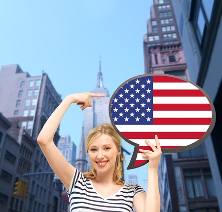 english text: education, foreign language, english, people and communication concept - smiling woman holding text bubble of american flag Stock Photo