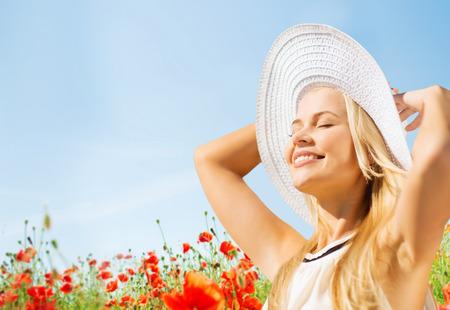 chapeau de paille: bonheur, nature, été, les vacances et les gens notion - souriante jeune femme avec les yeux fermés portant chapeau de paille sur le champ de pavot
