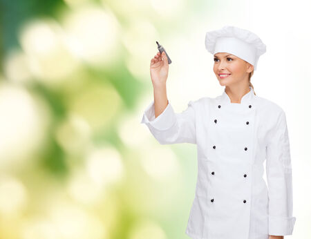 cooking, advertisement and people concept - smiling female chef, cook or baker with marker writing something on air over green background photo