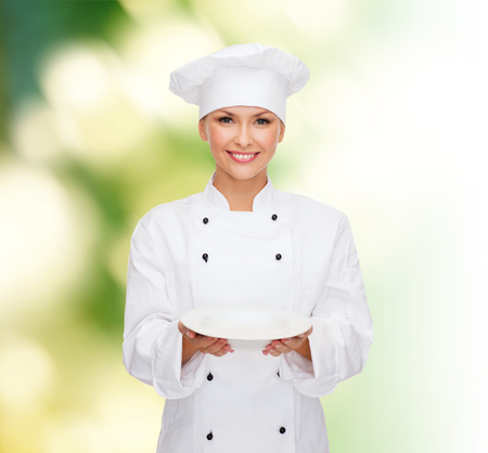 people, cooking and food concept - smiling female chef, cook or baker with empty plate over green background photo