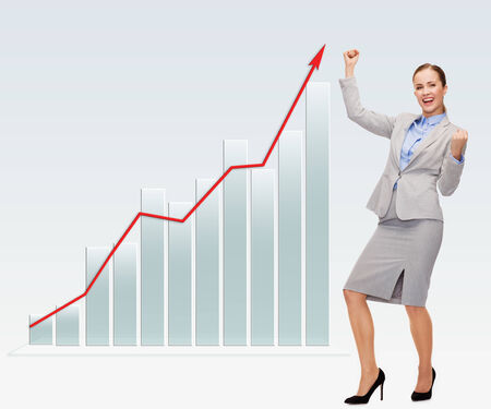 growing business: business, success, people and statistics concept - young happy businesswoman with hands up and graph over gray background Stock Photo