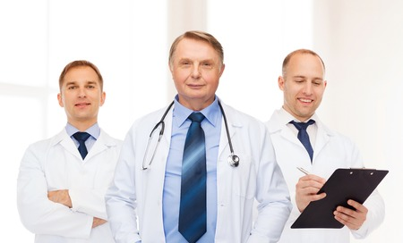 white coats: healthcare, profession and medicine concept - group of smiling male doctors in white coats with clipboard and stethoscope over clinic background Stock Photo