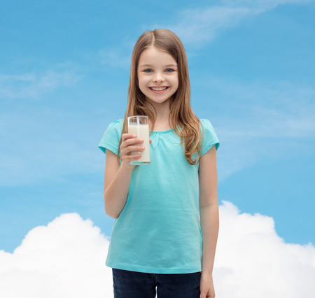 pre teen girls: health and beauty concept - smiling little girl with glass of milk